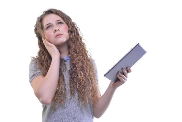 タブレットを片手に考える女性