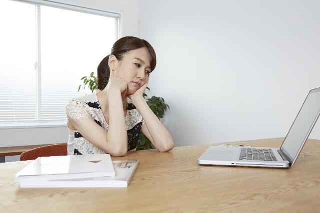パソコンを疲れ顔で見つめる女性
